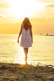 Girl is standing on the beach at sunset background royalty free stock photography