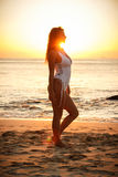 Girl standing on the beach in white swimming suit during sunset Royalty Free Stock Photos