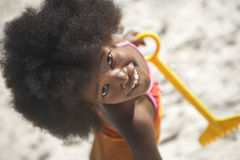 Girl (8-10) standing on beach with yellow toy spade, smiling, portrait, overhead view Royalty Free Stock Photos