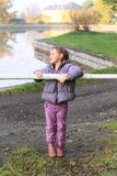 Girl standing behind banisters. Little kid - girl in lila clothes and brown shoes standing behind banisters in front of pond and preparing for training royalty free stock images