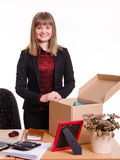 Girl standing behind an office desk with a big box Stock Photos