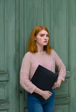 Girl standing with a black folder in hands Royalty Free Stock Photos