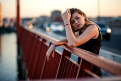 The girl is standing on a bridge in a black dress royalty free stock image