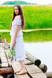 Girl standing on the bridge over the river with a bouquet Royalty Free Stock Images