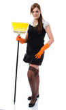 Girl standing with broom. Woman in sexy stockings standing with yellow broom - isolated on white background Stock Image