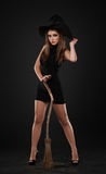 The girl is standing with the broom. In the studio Stock Photography