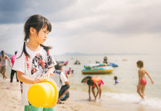 Girl is standing in busy beach looking out to the ocean. Royalty Free Stock Photos