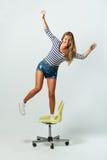 Girl standing on a chair balancing Stock Photos