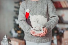 Girl standing at the Christmas tree and holding a toy horse. She`s wearing a gray sweater royalty free stock images