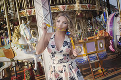 Girl standing in the city inflating bubbles against the background of the carousel Royalty Free Stock Image