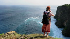 Girl standing on cliff's edge and taking photos stock video