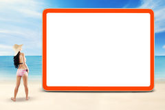 Girl standing at coast near the empty board Royalty Free Stock Photos