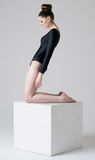 Girl standing on a cube. A beautiful sad girl standing on the big white cube Royalty Free Stock Photos