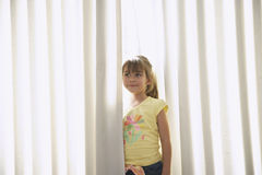 Girl Standing Between Curtains Stock Photo