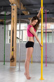 Girl standing by dancing pole Stock Images