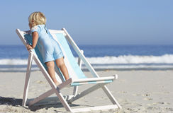 Girl (2-4) standing on deckchair on sandy beach, rear view, sea in background Stock Photo