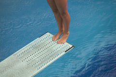 Girl standing on diving board. Legs on a diving board Royalty Free Stock Photos