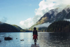 Girl Standing on Dock Facing the Wilderness Stock Photos