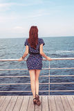 Girl standing on the dock watching the sea ocean. Girl standing on the dock watching the sea watching the ocean stock photo