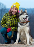 Girl standing with a dog Husky in the mountains. Girl standing with a dog Husky Stock Photo