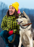 Girl standing with a dog Husky in the mountains. Girl standing with a dog Husky royalty free stock photos