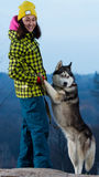 Girl standing with a dog Husky in the mountains. Girl standing with a dog Husky royalty free stock photo