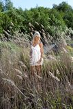 Girl are standing in dry grass Stock Image