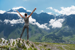 Girl standing edge of cliff and looking at mountain landscape Royalty Free Stock Photos