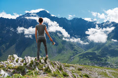 Girl standing edge of cliff and looking at mountain landscape Royalty Free Stock Photo