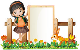 A girl standing beside an empty frame with a bunny Stock Photos