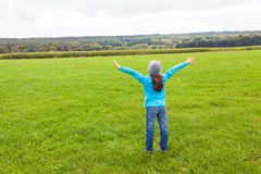 Girl standing in a field, arms stretched Stock Photos
