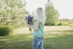 Girl is standing in the field with a bouquet of lupines. The girl is standing in the field with a bouquet of lupines Royalty Free Stock Photo