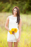 Girl standing in field with sunflowers Stock Photos