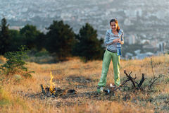 Girl standing by  fire on  camping Stock Images