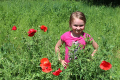 Girl standing in the flower-bed with red poppies Royalty Free Stock Photography