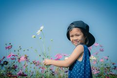 The girl is standing in the flower garden in the morning. Royalty Free Stock Photo