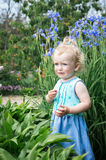 Girl is standing in the flower garden. Royalty Free Stock Photos