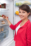 Girl standing by the fridge Royalty Free Stock Photography