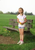 Girl standing in front of bench. Couriouse little girl standing in front of wooden bench and holding yellow flowers Stock Images