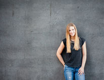 Girl standing in front of concrete wall Stock Photos