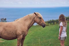 Girl standing in front of a light brown horse. Girl is standing in front of a brown horse, both are watching, scenery in front of the Atlantic Ocean on Sao Stock Photography