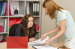 A girl standing in front of the office specialist shows her paper Stock Photos