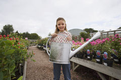 Girl (9-11) standing in garden centre, holding watering can, smiling, portrait Stock Photos