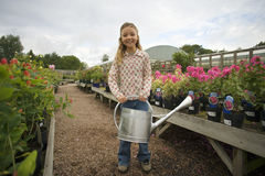 Girl (9-11) standing in garden centre, holding watering can, smiling, portrait Stock Images