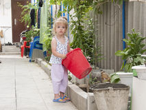 A girl standing in the garden with a red bucket Stock Image