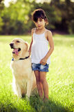 Girl standing in grass with golden retriever Royalty Free Stock Photos