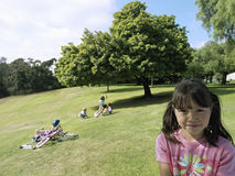 Girl (7-9) standing on grass in park, friends playing near bicycles, focus on foreground, portrait royalty free stock image