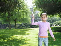 Girl (7-9) standing on grass in park, listening to MP3 player, eyes closed, smiling royalty free stock photos