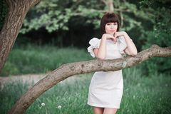 Girl standing in greens. Beautiful young woman in a white dress standing near the tree among greens in a park Stock Photography