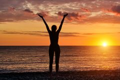 Girl standing hands up on the beach at sunset. Silhouette royalty free stock photos
